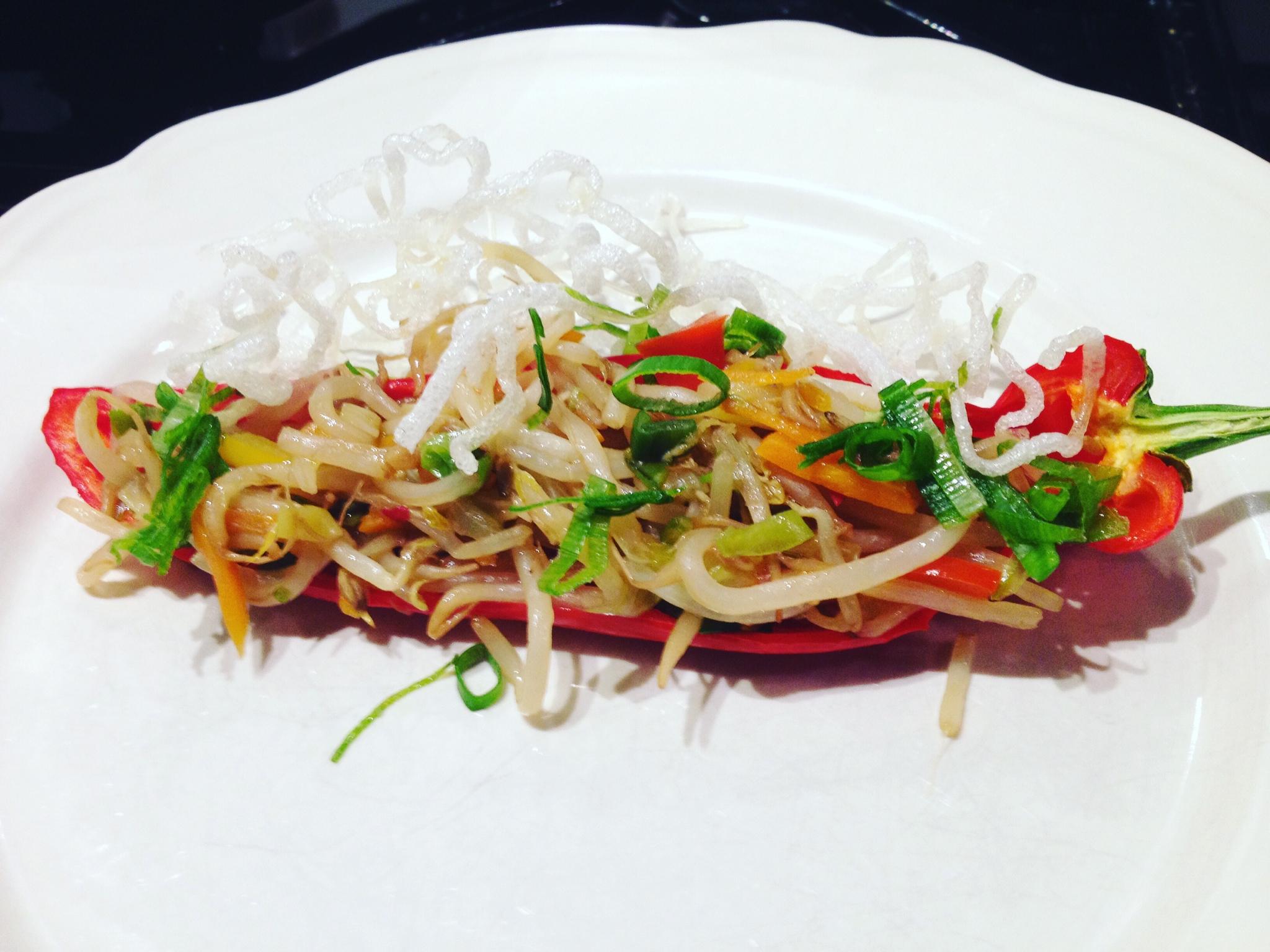 Breng een wok eens op een andere manier op tafel.  Zoals op de foto in een lange zoete paprika met gefrituurde rijstnoedels.